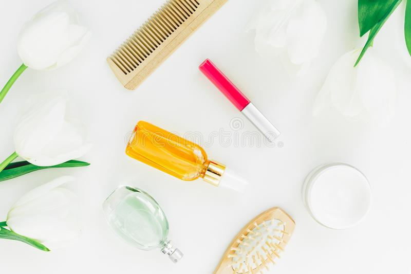 Cosmetics, perfume, combs and tulips flowers on white background. Beauty blogger composition. Flat lay, top view stock photos
