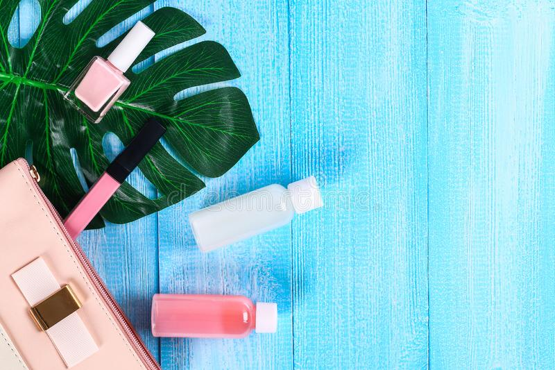 Cosmetics in a pink cosmetic bag. Lip gloss, cream, nail polish, skin care products on a tropical leaf on a blue wooden background.  stock photography