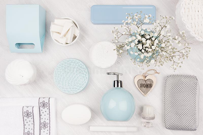 Cosmetics products as art background - set for body and skin care, blue ceramic bowl, silver accessories, flowers, heart, box. Cosmetics products as art stock image