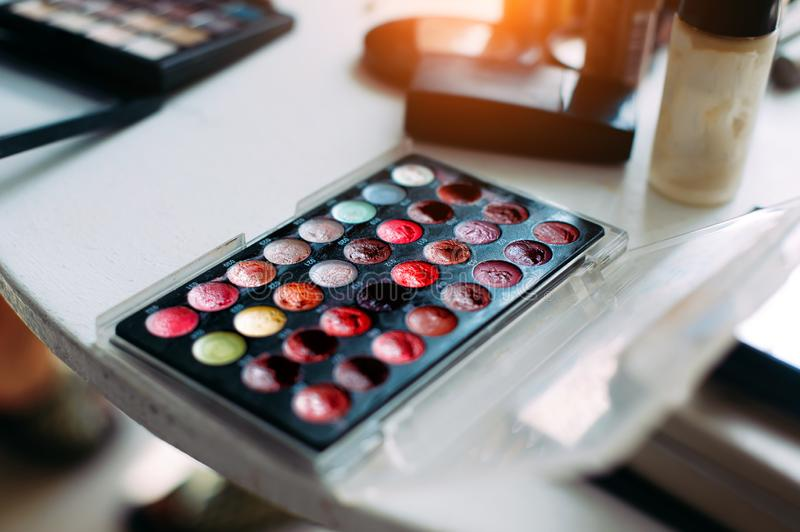 Cosmetics for professional makeup. Makeup artist set, close-up. Cream eye shadows, a blush, palette of colors stock photos