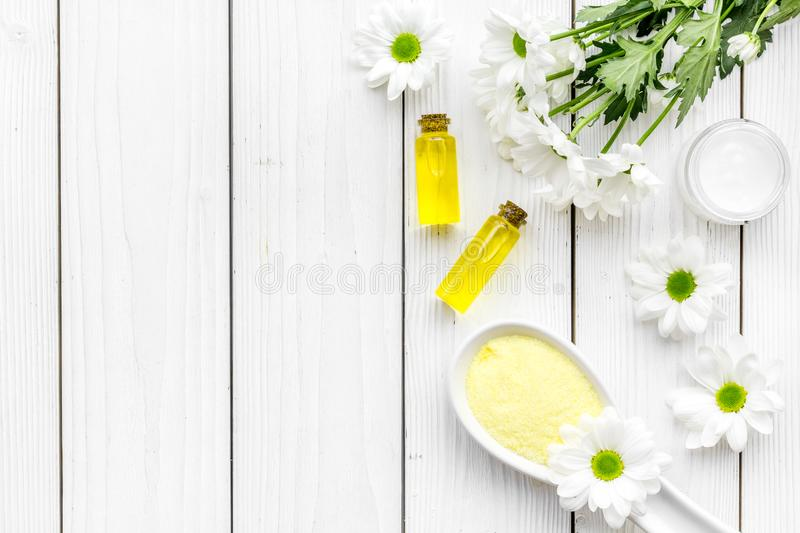 Cosmetics for skin care with chamomile. Chamomile oil, cream, spa salt on white wooden background top view copy space. Cosmetics for skin care with chamomile stock photography