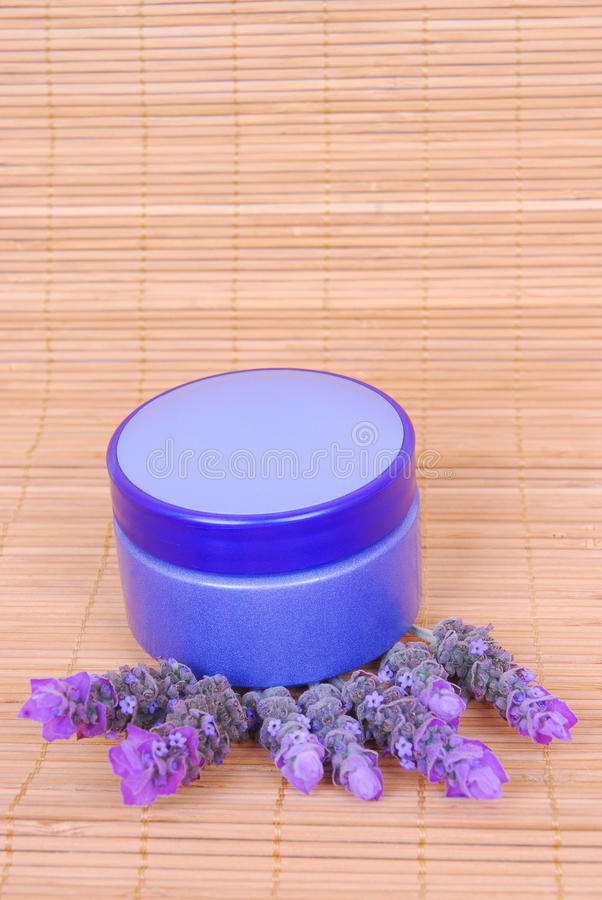 Cosmetics in spa. A little purple pot of luxury cosmetic creme on freshly picked lavender blossoms. Image on bamboo background royalty free stock photos
