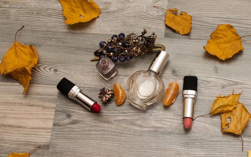 Cosmetics on a wooden background with autumn leaves. Autumn makeup concept.  royalty free stock photos