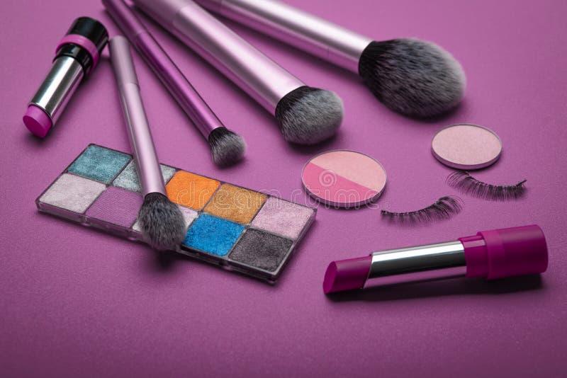Cosmetische set van verschillende schoppen, compact en los gelaatpoeder, bronzed parels, verhulling en make-uppenseel op paarse a stock afbeeldingen