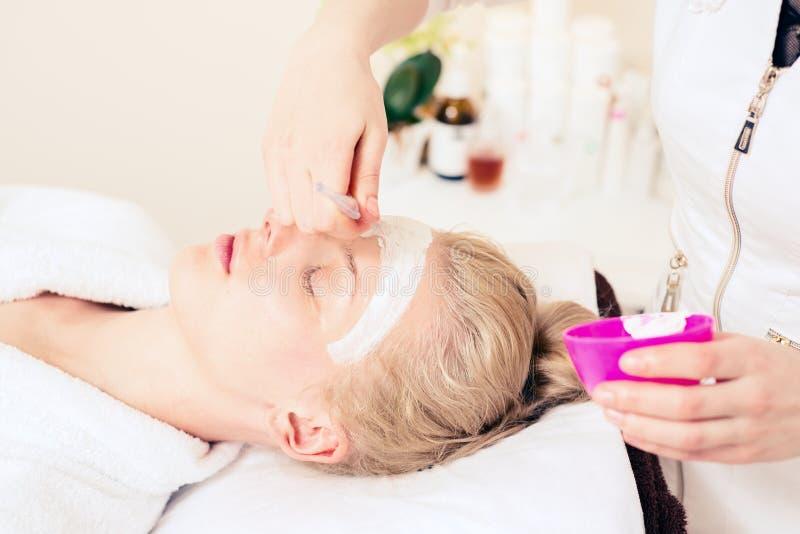 Cosmetologia della stazione termale il cosmetologo di medico applica la crema per affrontare ragazza che si preoccupa per la pell immagine stock libera da diritti