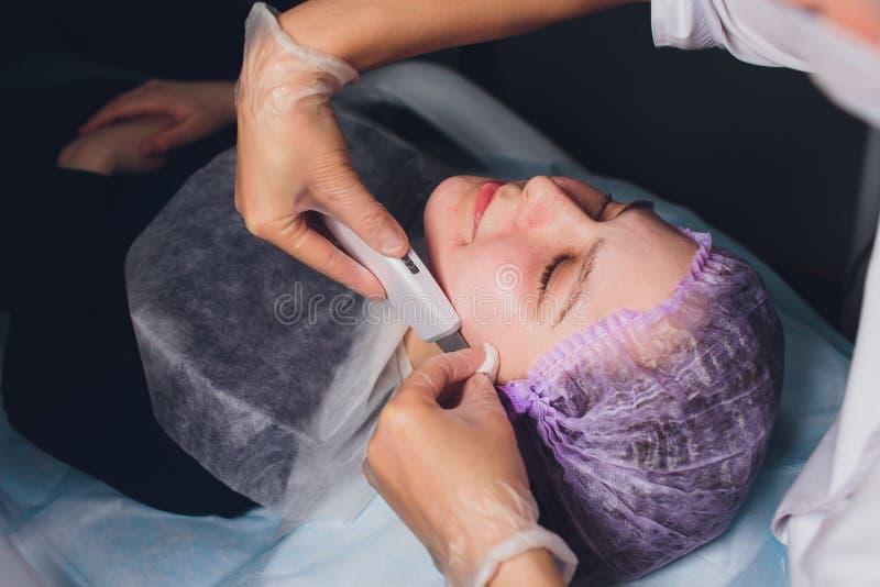 Cosmetologia do hardware O esteticista faz o ultrassom chromotherapy que limpa a cara do cliente Limpeza do poro da pele anti fotografia de stock