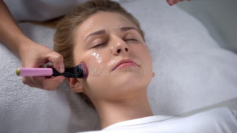 Cosmetologist που βάζει τη μάσκα άλατος αλγινικού οξέος στο πρόσωπο πελατών, ενυδάτωση, φροντίδα δέρματος στοκ φωτογραφίες