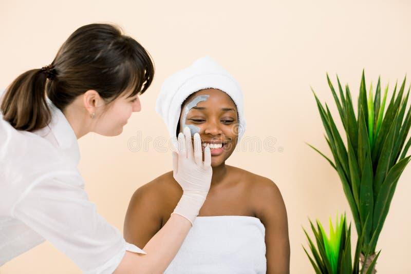 Cosmetologist που εφαρμόζει τη μάσκα επάνω στο πρόσωπο της γυναίκας αφροαμερικάνων στο σαλόνι SPA Ομορφιά και έννοια φροντίδας δέ στοκ φωτογραφία
