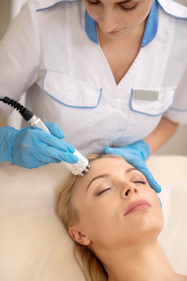 Cosmetologist που κάνει τη σκλήρυνση δερμάτων υπερήχου για τον πελάτη στοκ φωτογραφίες