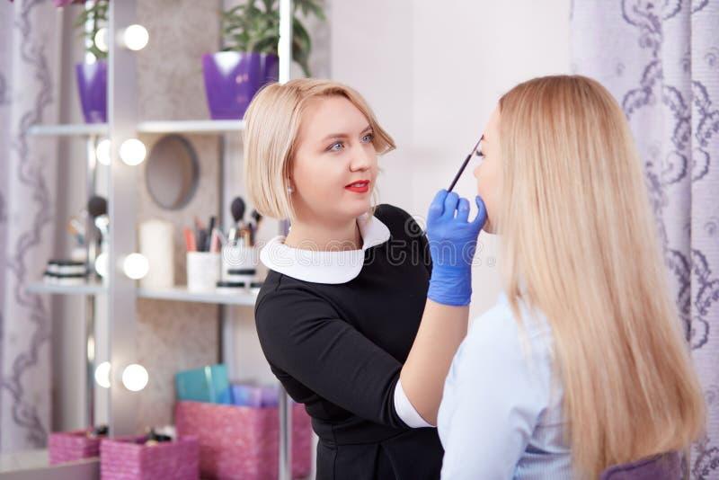 Cosmetologist που κάνει το μόνιμο makeup των φρυδιών στοκ εικόνα