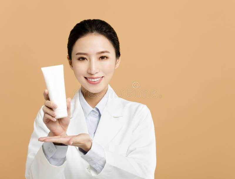 Cosmetologist που παρουσιάζει προϊόν ομορφιάς στοκ φωτογραφίες