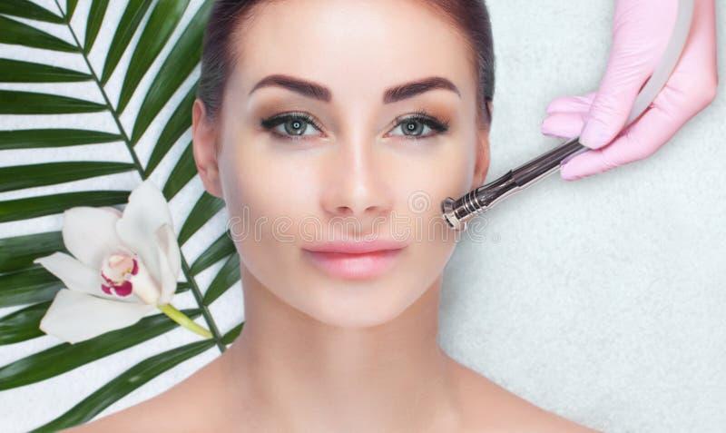 Cosmetologist делает процедуру Microdermabrasion лицевой кожи красивого, молодой женщины в салоне красоты стоковая фотография