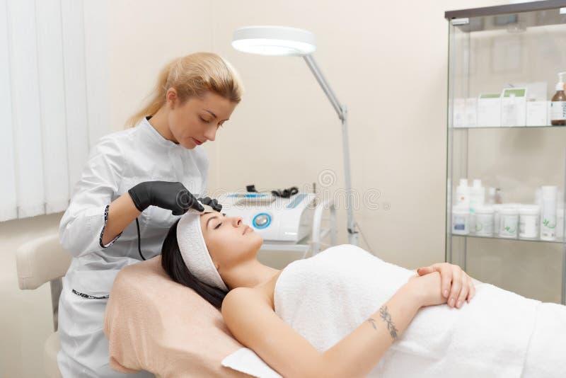 Cosmetologist делая косметологию оборудования процедуры стоковое изображение rf