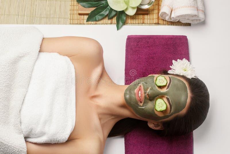 Cosmetologist мажет косметическую маску на стороне женщины в салоне спа Маска глины спа на стороне femele Skincare Уход за лицом стоковое изображение
