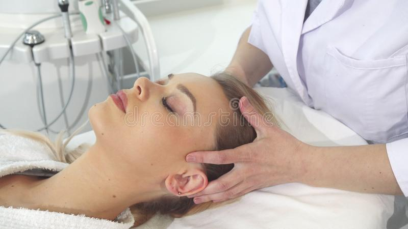 Cosmetologist массажирует голову ` s клиента стоковое изображение