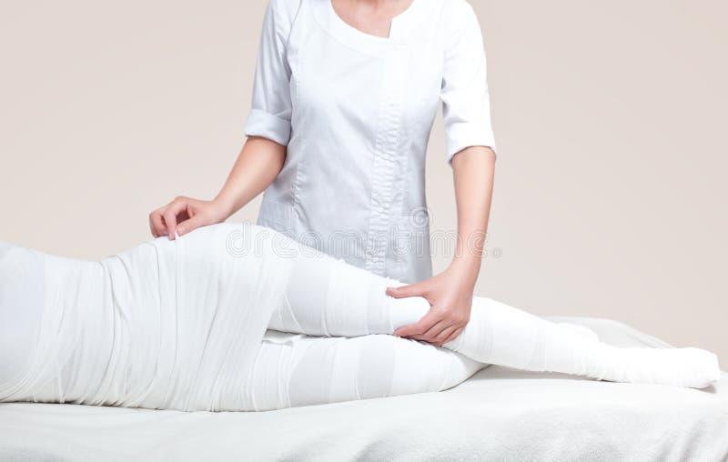 Cosmetologist оборачивает ногу клиента процедура по Анти--целлюлита стоковые фото