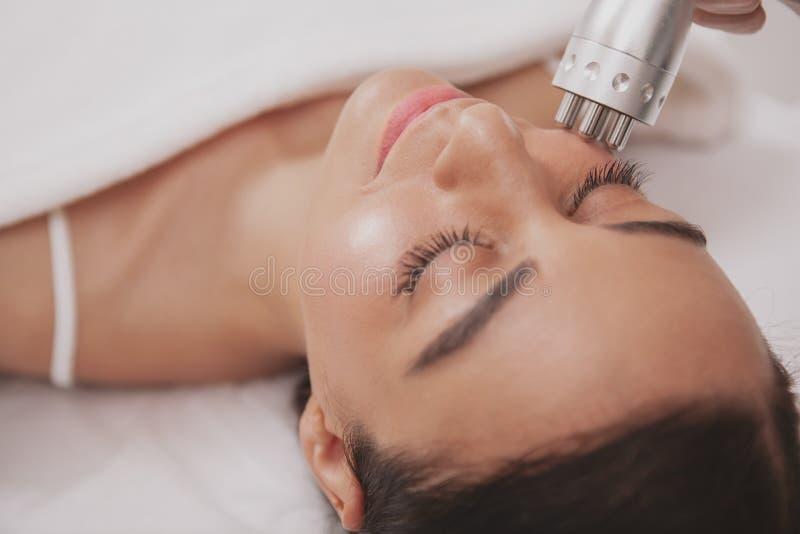 Cosmetologist прекрасной молодой женщины посещая на клинике красоты стоковое изображение rf