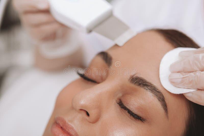 Cosmetologist прекрасной молодой женщины посещая на клинике красоты стоковое фото