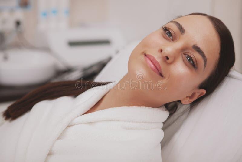 Cosmetologist прекрасной молодой женщины посещая на клинике красоты стоковое изображение