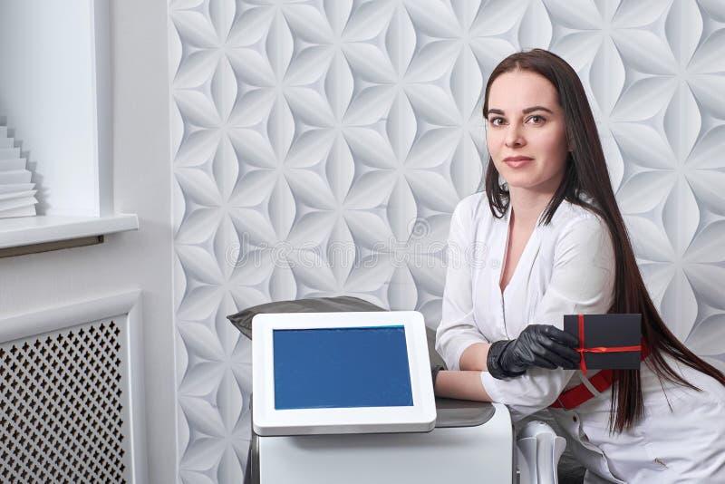 Cosmetologist с прибором косметологии IPL Обслуживание удаления лазера волос Прибор лазера СИД косметики для фотодинамического стоковое изображение rf