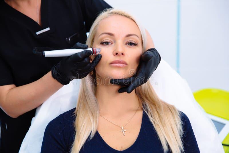 Cosmetologist уносит процедуры на стороне пациента с прибором гидро-шелушения Очищать и подмолаживание стоковое фото rf