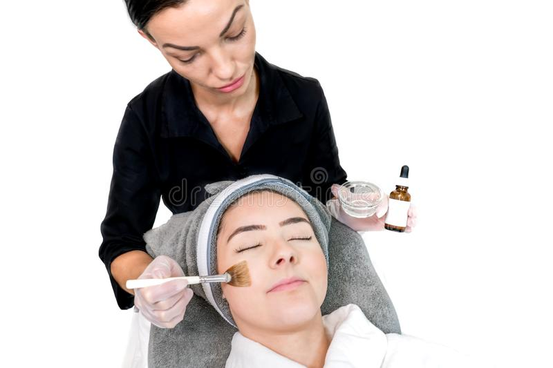 Cosmetologist administering chemical peel treatment on patient in a beauty spa, for skin rejuvenation, complexion and acne beauty. Treatments. Two females in a royalty free stock image