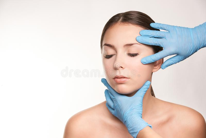 Cosmetologist apply mentoplasty. Beauty girl skin do Facelift at cosmetology spa. Women model treatment stock photo