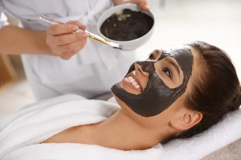 Cosmetologist applying black mask onto woman`s face. In spa salon stock images