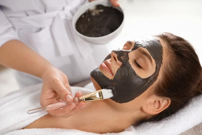 Cosmetologist applying black mask onto woman`s face. In spa salon stock photo
