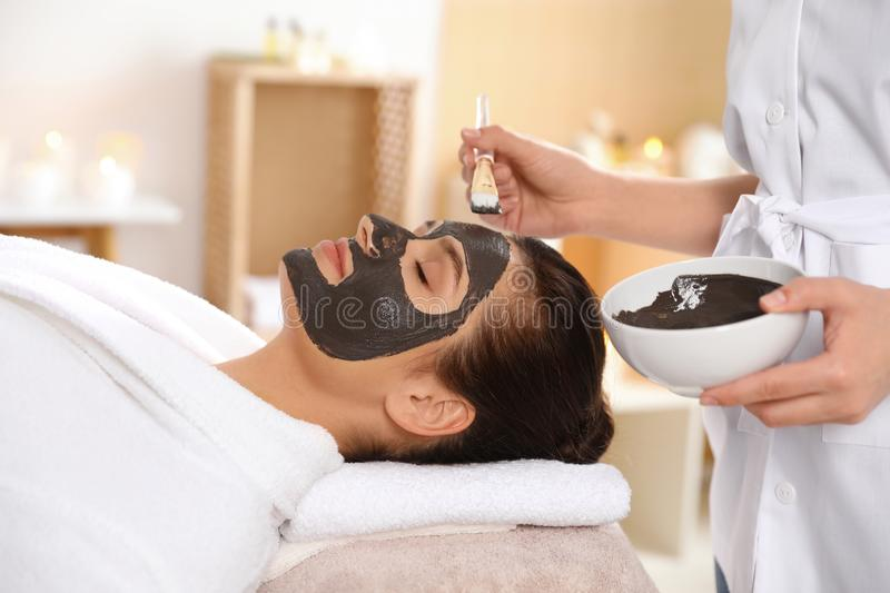 Cosmetologist applying black mask onto woman`s face. In spa salon royalty free stock images
