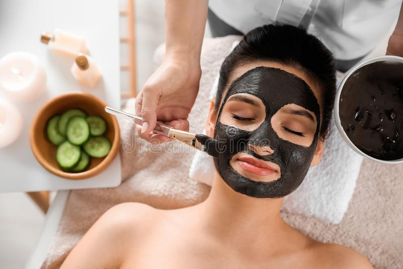 Cosmetologist applying black mask onto woman`s face. In spa salon, top view royalty free stock photo