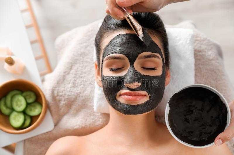 Cosmetologist applying black mask onto woman`s face. In spa salon, top view stock images