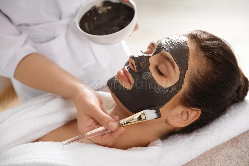 Cosmetologist applying black mask onto woman`s face. In spa salon royalty free stock photos