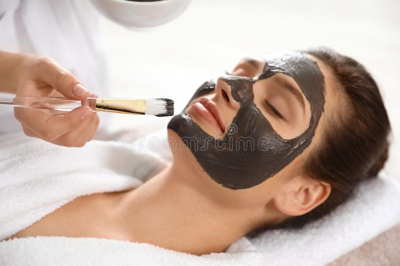 Cosmetologist applying black mask onto woman`s face. In spa salon stock photography