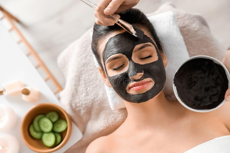 Cosmetologist applying black mask onto woman`s face in spa salon. Top view royalty free stock photos
