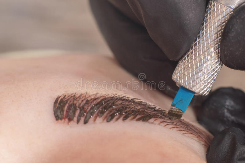 Cosmetologist applying permanent make up on eyebrows. stock photo