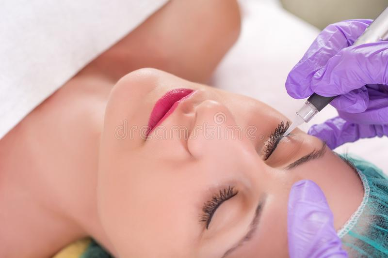 Cosmetologist applying permanent makeup on eyes royalty free stock photography