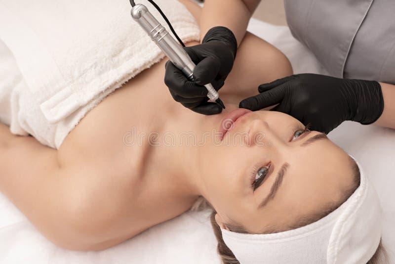 Cosmetologist applying permanent tattoo make up on lips stock photo