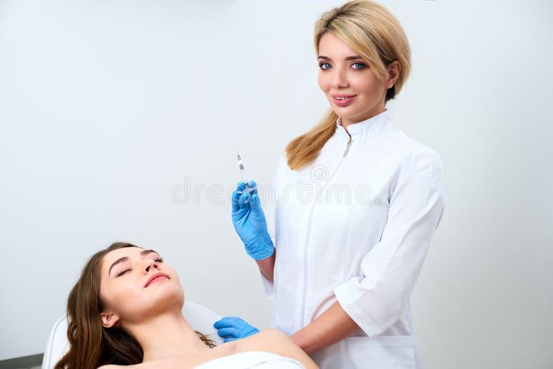 Cosmetologist arts die zich dichtbij pati?nt bevinden en botulinum spuit houden die handschoenen v??r verrichting, injecties drag royalty-vrije stock afbeeldingen