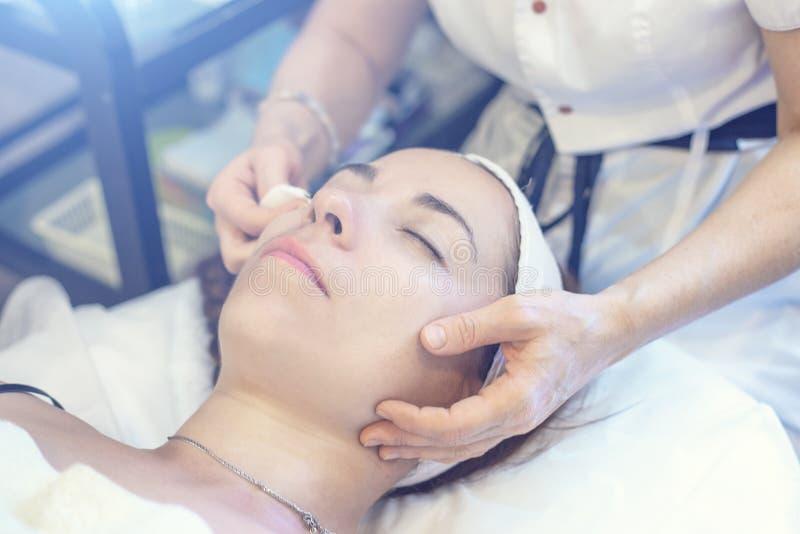 Cosmetologist avec la patiente de jeune femme dans la clinique Procédure de épluchage et de nettoyage pour le rajeunissement faci images stock