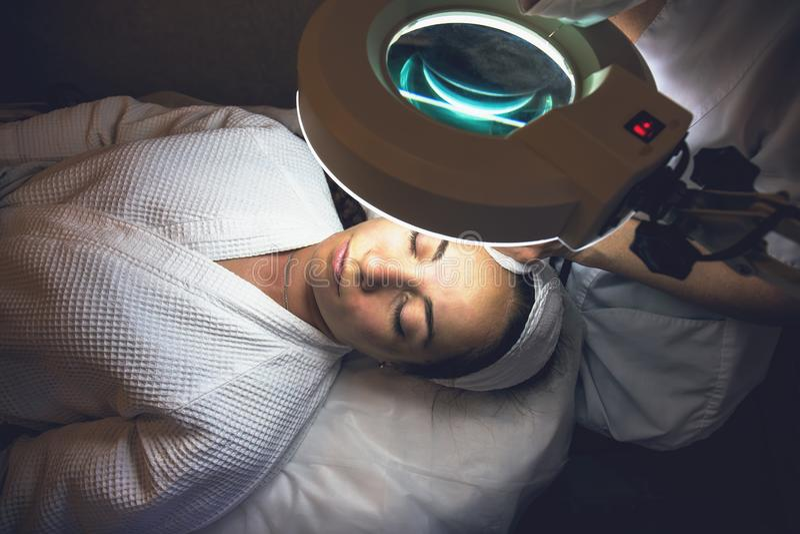 Cosmetologist avec la patiente de jeune femme dans la clinique, vue supérieure Procédure de épluchage et de nettoyage pour le raj image stock