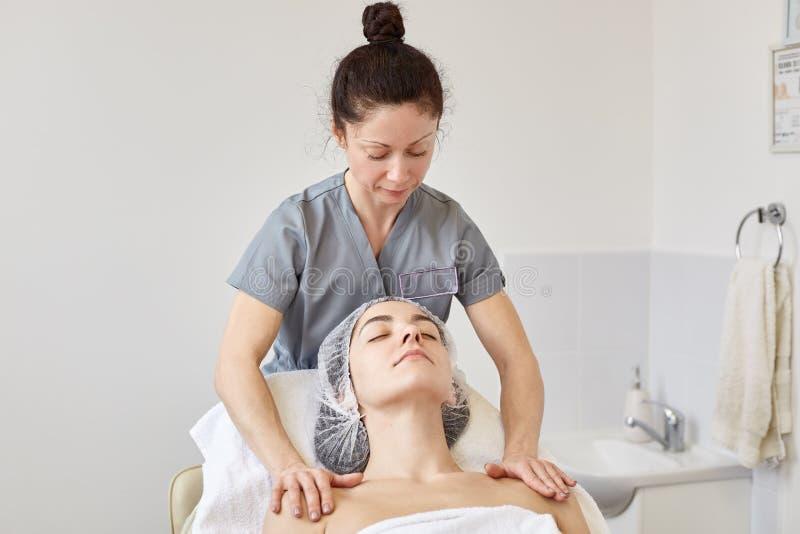 Cosmetologist bekijkt haar cliënt, die haar handen op schouders zetten, makend schoonheidsprocedures Kalm model die op kosmetisch stock fotografie