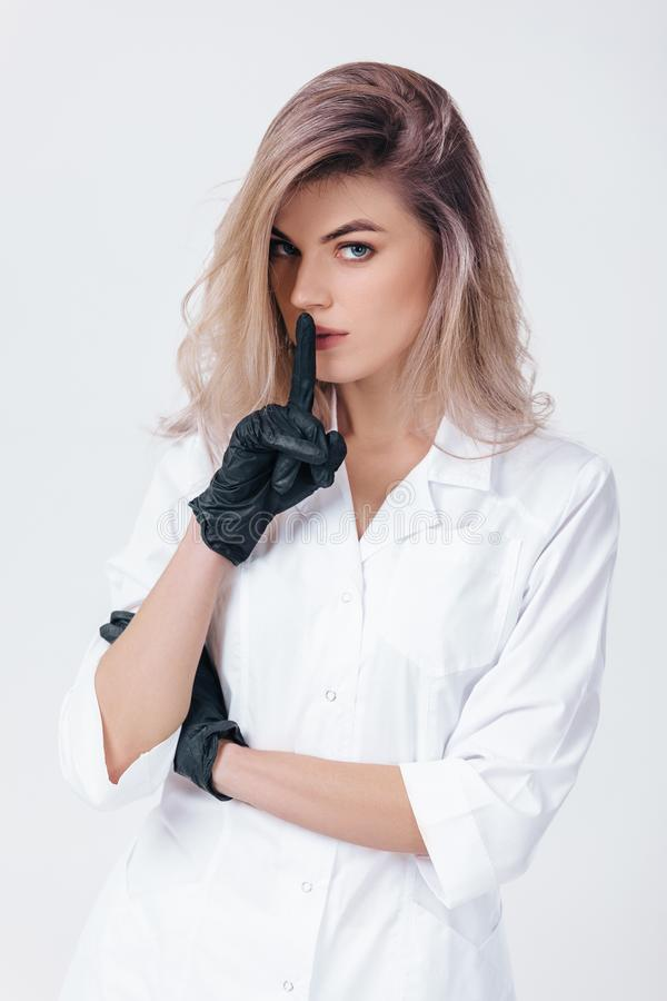 Cosmetologist in black gloves shows sign silence. Woman beautician doctor. Portrait of young female professional doctor in black gloves shows sign silence royalty free stock photo