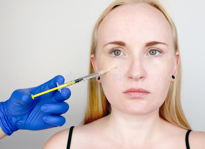 A cosmetologist carries out a procedure - an injection into the face of a young woman. Beauty injections, mesotherapy, hyaluronic stock images