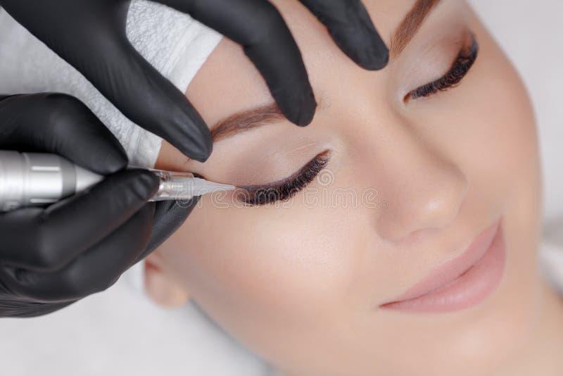 Cosmetologist che fa trucco permanente immagine stock libera da diritti