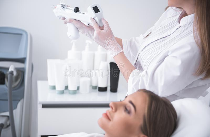 Cosmetologist checking syringe gun while beautiful young lady waiting for procedure royalty free stock images