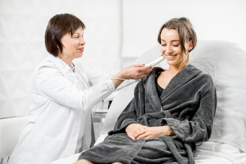 Cosmetologist con el cliente en el centro médico fotografía de archivo