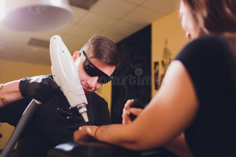 Cosmetologist con el paciente y el laser profesional del retiro del tatuaje en sal?n imágenes de archivo libres de regalías
