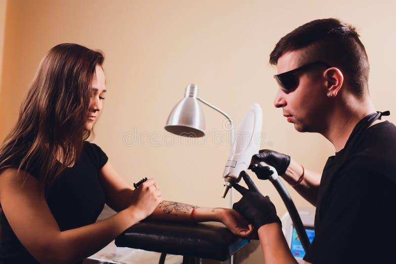 Cosmetologist con el paciente y el laser profesional del retiro del tatuaje en sal?n foto de archivo libre de regalías