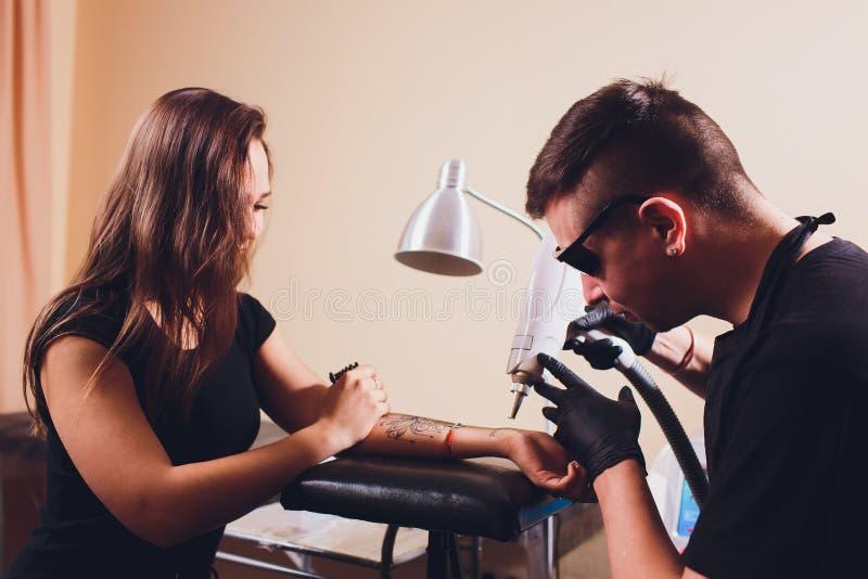 Cosmetologist con el paciente y el laser profesional del retiro del tatuaje en sal?n fotografía de archivo